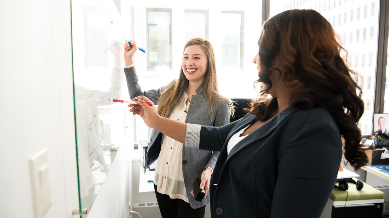 Two women smiling and writing on whiteboard in the office.