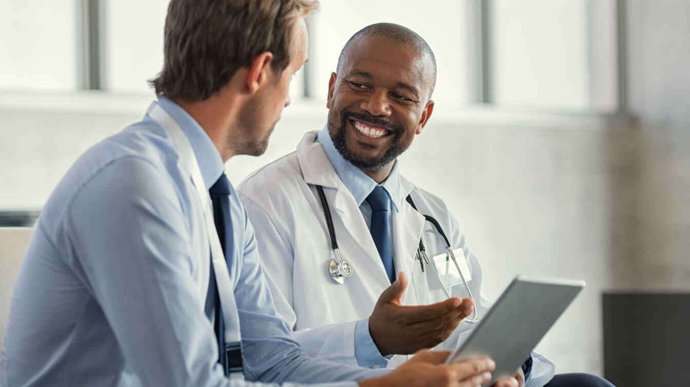 Male doctor smiling at patient while holding his tablet.
