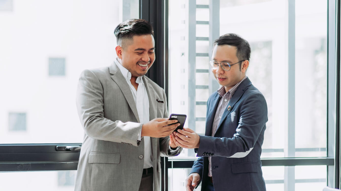 Two professionals looking at insights on a device.
