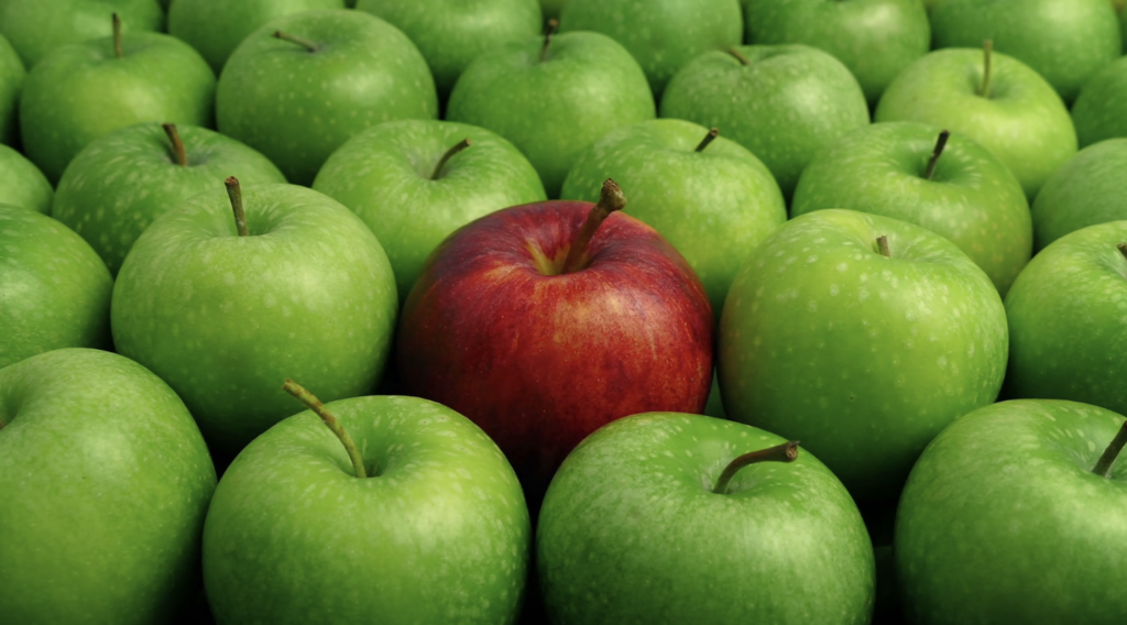 A group of green apples with one red apple